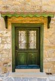 Zielony drewniany drzwi z dokonanym żelazem kamienny budynek Zdjęcie Stock