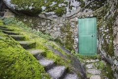 Zielony drzwi na dużym kamieniu Obrazy Stock