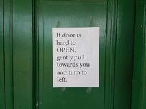Zielony drzwi z instrukcjami dlaczego otwierać Fotografia Royalty Free