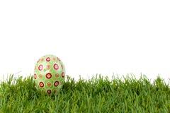 Zielony Easter jajko na zielonej trawie na białym odosobnionym tle Obraz Stock