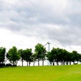 Zielony energii odnawialnej pojęcie - wiatrowego generatoru turbina w chmurnym niebie na zielonej trawy łące Zdjęcie Royalty Free