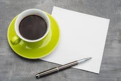 Zielony filiżanka kawy z czystą pieluchą i metalu ballpoint pióro na popielatym tle fotografia stock