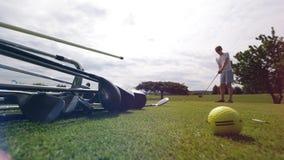 Zielony gazon z klubami i męski gracz bierze strzał zbiory