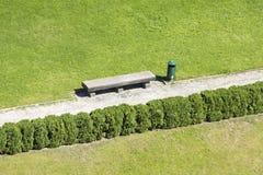Zielony gazon z parkowej ławki, żywopłotu i śmieci koszem, Zdjęcia Royalty Free