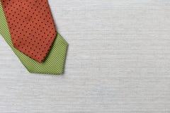Zielony i czerwony krawat na brezentowej teksturze Obrazy Stock