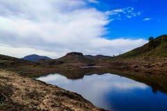 Zielony i kamienisty góra krajobraz z jeziorem i niebieskie niebo z c zdjęcie stock