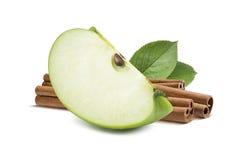 Zielony jabłko ćwiartki kawałka cynamon w plecy odizolowywającym zdjęcia royalty free