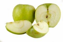 Zielony jabłko i dwa plasterka z ziarnami na białym tle obraz stock