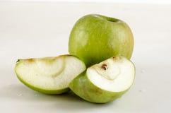 Zielony jabłko i dwa plasterka z ziarnami na białym tle zdjęcia royalty free