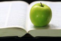 Zielony jabłko na książce Zdjęcie Stock