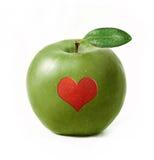 Zielony jabłko odizolowywający z czerwonym sercem fotografia royalty free