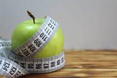 Zielony jabłko przekręcający pomiarową taśmą obrazy stock