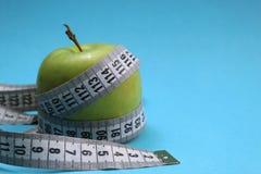 Zielony jabłko przekręcający pomiarową taśmą fotografia royalty free