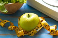Zielony jabłko z ciężar skala i pomiarową taśmą dla zdrowej diety odchudzania Fotografia Stock