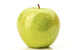 Zielony jabłko z kropelką na bielu obrazy stock