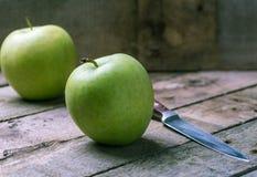 Zielony jabłko z nożem na drewnianym naturalnym biurku Obrazy Royalty Free