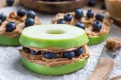 Zielony jabłko zaokrągla z masłem orzechowym i czarnymi jagodami na drewnianym stole i, horyzontalnym obrazy stock