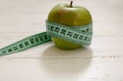 Zielony jabłko zawijający w centymetrze na białym drewnianym tło dowcipie zdjęcie royalty free