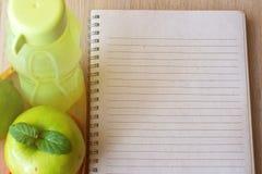 Zielony jabłko, wapno, bidon i pusty notatnik na lekkim drewnianym tle, Obraz Royalty Free