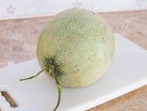 Zielony japoński melon na białym bloku w kuchni Obrazy Stock