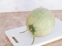 Zielony japoński melon na białym bloku w kuchni Obrazy Royalty Free