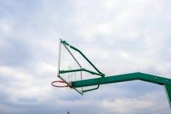 Zielony koszykówka stojak z szklanym backboard w chmurnym niebie zdjęcie royalty free