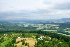 Zielony krajobraz z drzewami, domami i odległymi wzgórzami, Zdjęcia Royalty Free