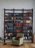 Zielony krzesło w wnętrzu Bookcase z starymi książkami na półkach Książki w starym drewnianym gabinecie zdjęcie stock