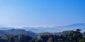 Zielony lasowy wzgórze i niebieskie niebo z chmurami Zdjęcia Stock
