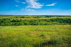 Zielony natura krajobraz z obszarów trawiastych wzgórzami i niebieskim niebem, spokojna wieś Obrazy Royalty Free