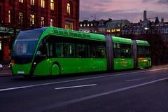 Zielony nowożytny autobus rusza się w mieście w wieczór Zdjęcie Stock