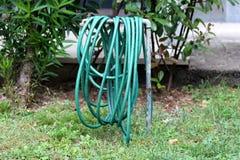 Zielony ogród wody wąż elastyczny zawijający wokoło metal drymby otaczającej z wysoką uncut trawą i drzewami w tle zdjęcie royalty free