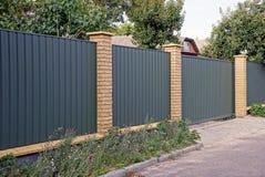 Zielony ogrodzenie i brama w ulicie blisko kwiatu łóżka blisko drogi Obraz Royalty Free