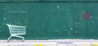 Zielony płotowy tło Odbitkowa przestrzeń obok supermarket fury na bruku fotografia royalty free