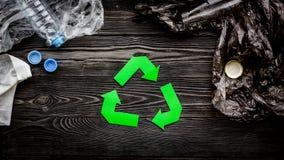 Zielony papier przetwarza znaka wśród jałowych polietylen toreb i klingeryt butelek na popielatego drewnianego tła odgórnym widok obraz stock