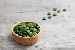 Zielony pigułki spirulina lub chlorella gałęzatka w drewnianym pucharze Obrazy Royalty Free
