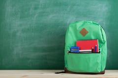 zielony plecak, kalkulator i notatnik na tle blackboard, obraz stock