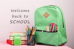 Zielony plecak, tekst & x22; Powitanie z powrotem school& x22; i szkolne dostawy: notepad, książki, nożyce, kalkulator fotografia stock