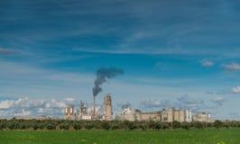 Zielony pole I fabryka Z zmroku dymu przybyciem Z kominu Fotografia Stock