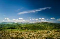 Zielony pole z chmurami Obraz Royalty Free