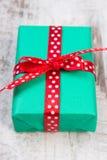 Zielony prezent dla bożych narodzeń lub innego świętowania na drewnianej desce Fotografia Stock