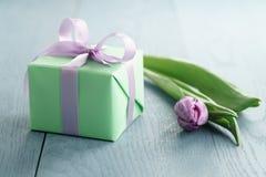 Zielony prezenta pudełko z purpurami ono kłania się i tulipan na błękitnym drewnianym tle Obrazy Stock