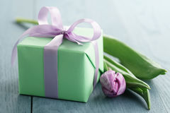 Zielony prezenta pudełko z purpurami ono kłania się i tulipan na błękitnym drewnianym tle Obraz Stock