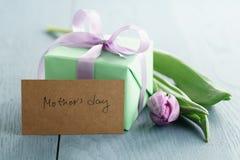 Zielony prezenta pudełko z purpurami ono kłania się i tulipan na błękitnym drewnianym tle z matka dnia kartka z pozdrowieniami Zdjęcia Royalty Free