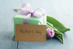Zielony prezenta pudełko z purpurami ono kłania się i tulipan na błękitnym drewnianym tle z matka dnia kartka z pozdrowieniami Zdjęcia Stock