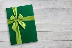 Zielony prezenta pudełko na drewnianym tle Obraz Royalty Free