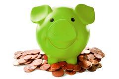 Zielony prosiątko bank wśród monet obrazy stock