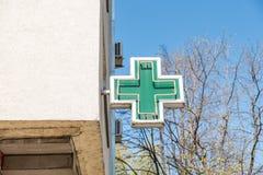 Zielony przecinający apteka znak, symbol na budynku fasadowym widoku od ulicy lub fotografia royalty free
