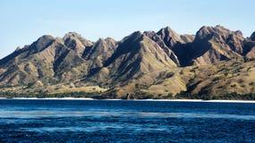 Zielony roślinności góry krajobraz z bielu plażowym i błękitnym linii brzegowej morzem przy swój stopą Zdjęcie Royalty Free