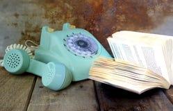 Zielony rocznika telefon i otwiera książkę na drewnianym stole Zdjęcia Royalty Free
